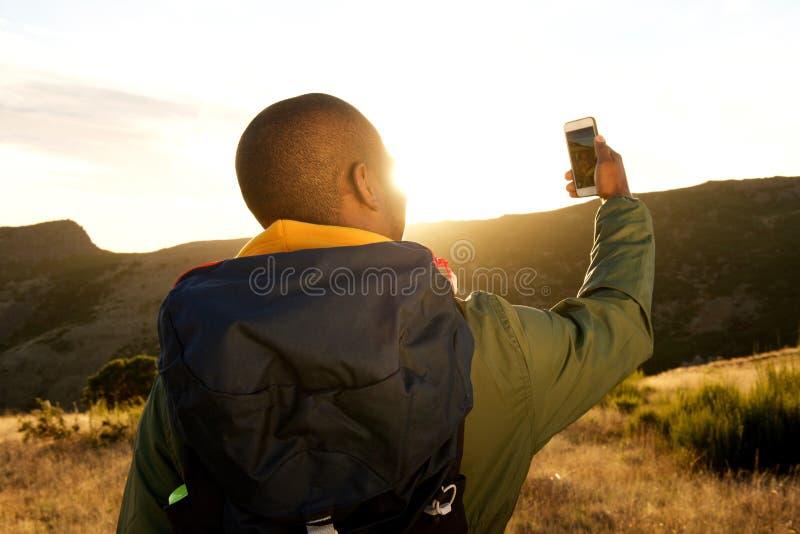 Atrás do homem afro-americano que caminha com o telefone celular que toma o selfie nas montanhas fotografia de stock royalty free