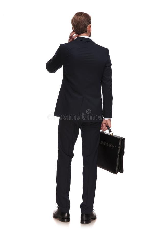 Atrás do homem de negócios pensativo que guarda a mala de viagem e que olha ao si imagem de stock