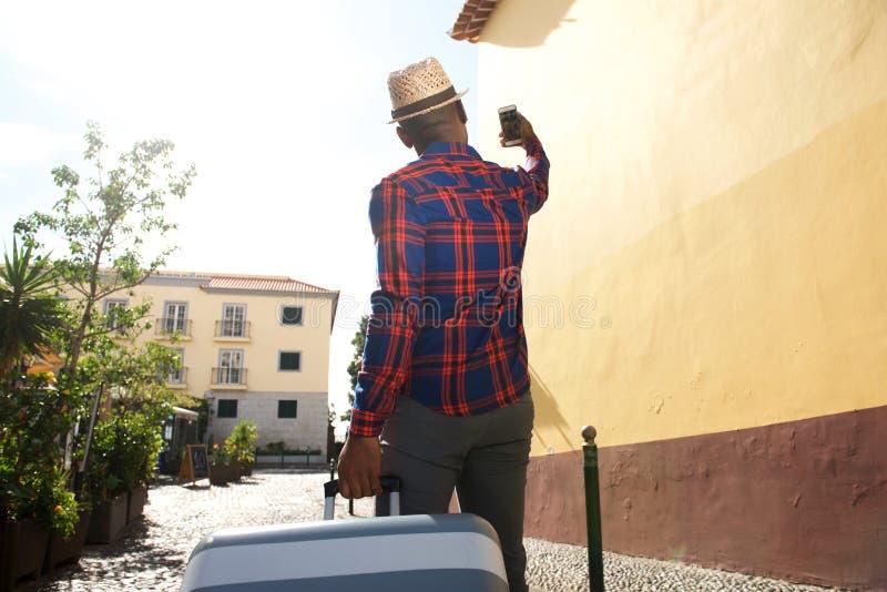 Atrás do homem de viagem preto que toma o selfie com telefone celular fotos de stock