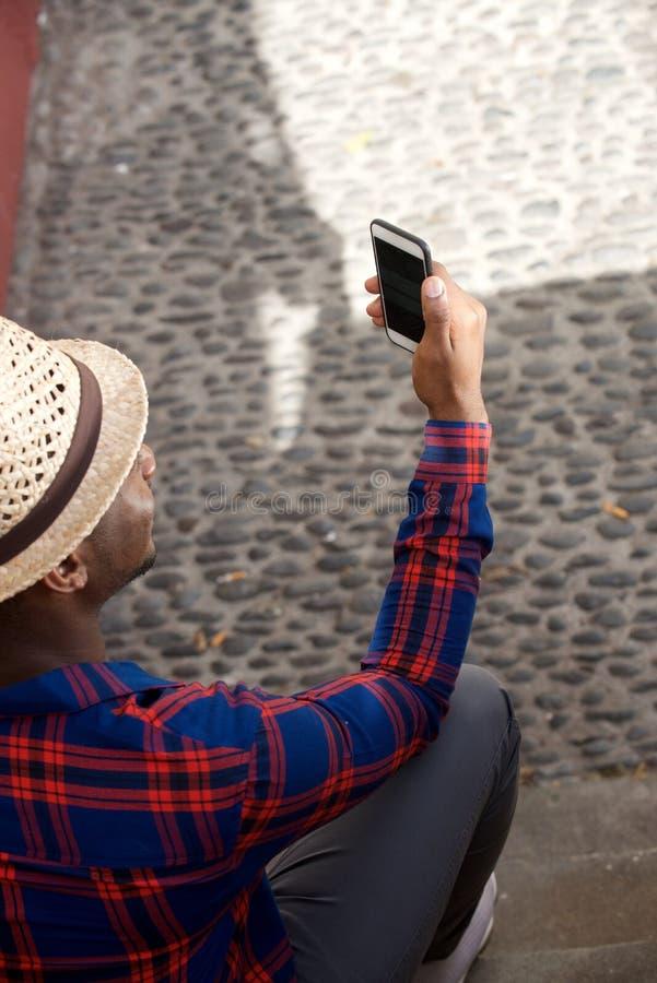 Atrás do homem negro novo com chapéu e de olhar o telefone celular imagem de stock