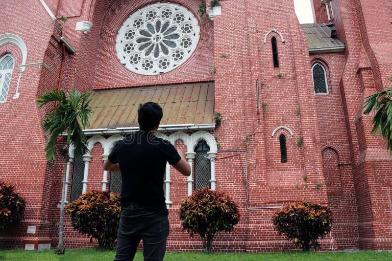 Atrás do homem que está na frente da construção principal da igreja e da torre de igreja na catedral do trinity santamente fotografia de stock