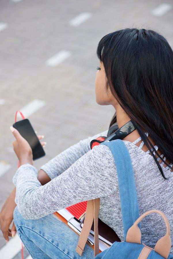 Atrás do telefone celular da terra arrendada do estudante fêmea fotos de stock royalty free