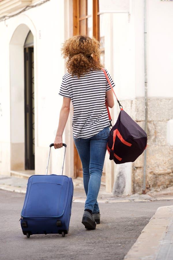 Atrás do viajante fêmea com mala de viagem e dos sacos que andam na rua imagens de stock royalty free