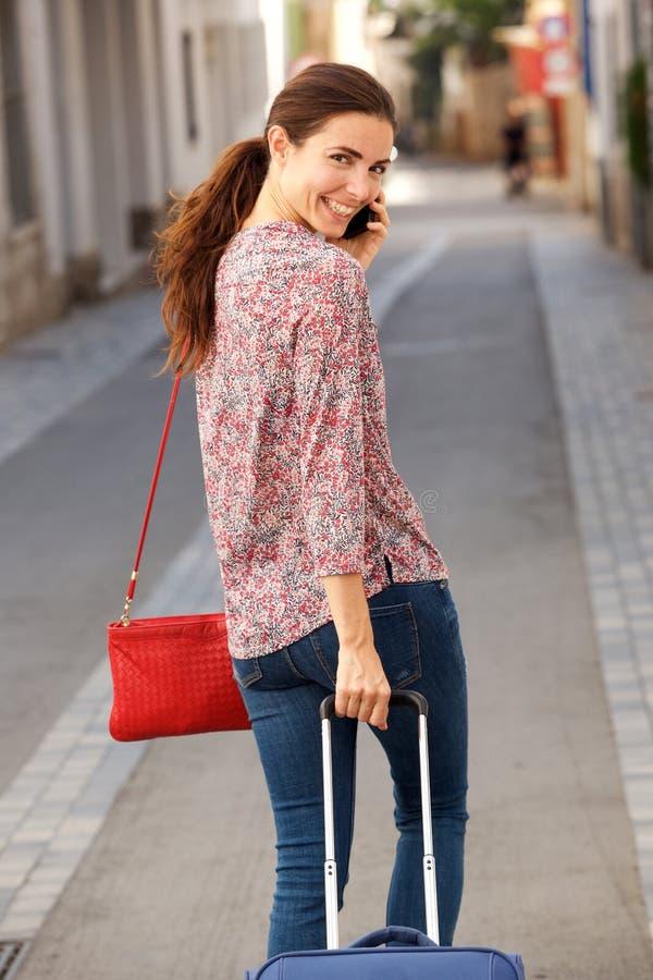 Atrás do viajante fêmea novo que anda na rua com bagagem e que usa o telefone celular fotos de stock