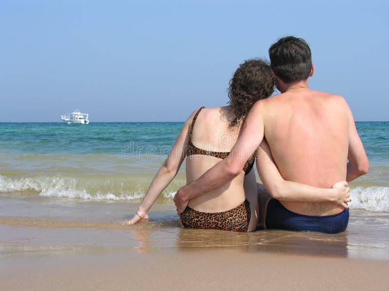 Atrás dos pares sente-se na praia fotografia de stock royalty free
