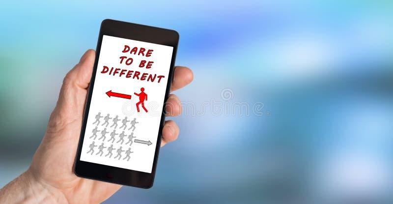Atrévase a ser diverso concepto en un smartphone imágenes de archivo libres de regalías