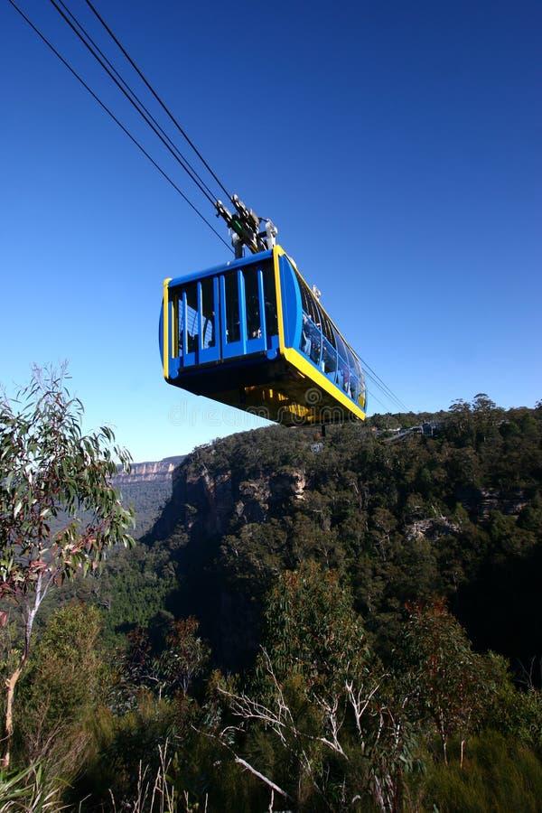 Atração turística da estrada de ferro aérea com o teleférico amarelo e azul do passageiro acima da vegetação no parque nacional d foto de stock