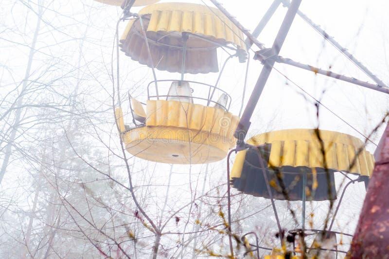 Atracción amarilla de la noria en niebla en el parque de atracciones abandonado demasiado grande para su edad con los árboles fotos de archivo
