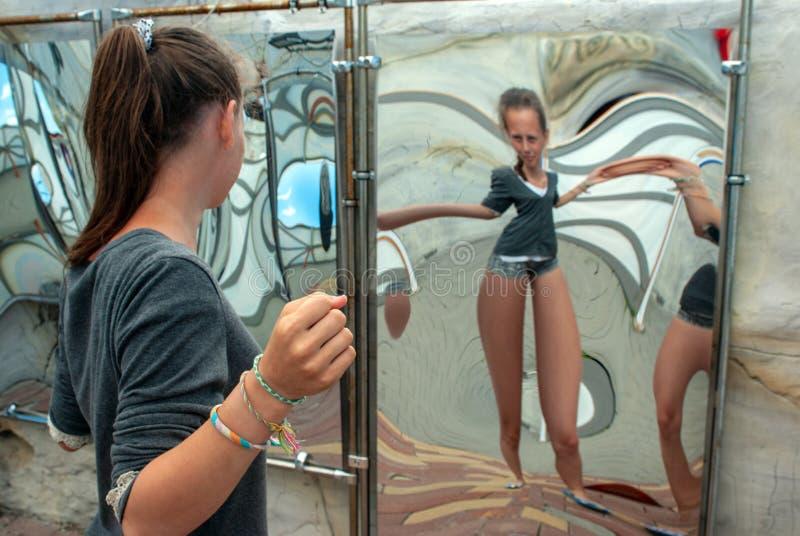 Atracción, muchacha que mira su imagen en el espejo torcido en el pasillo de espejos fotografía de archivo