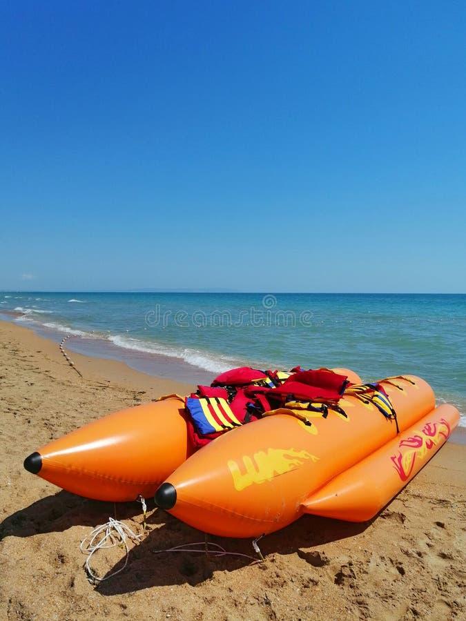 Atracci?n del mar barco de plátano inflable en la playa imagenes de archivo