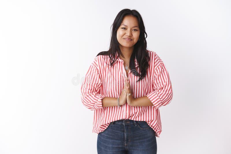 Atractiva joven polinesia de 20 años, con blusa a rayas, presione las palmas juntas en un gesto de bienvenida educado diciendo 'n fotos de archivo