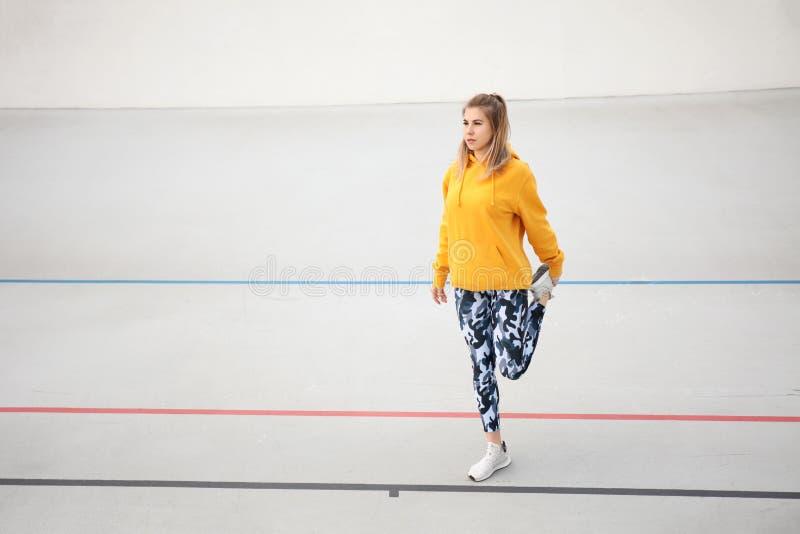 Atractiva mujer haciendo músculos calientes antes de entrenar El buen estado físico y el deporte matutino como estilo de vida Ext fotografía de archivo