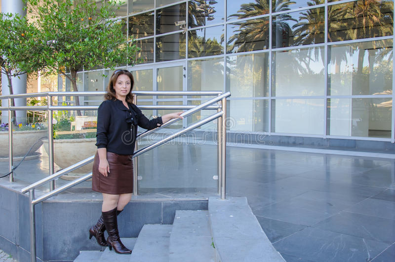 Atractive Business woman standing on the stairs of office building stock images