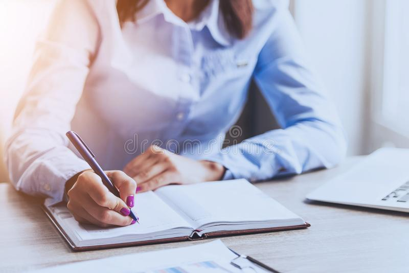 Businesswoman Writing in Notebook in Office . stock image