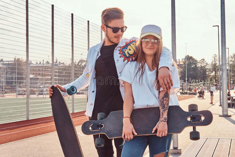 Atractive couple of trendy dressed young hipsters posing with skateboards at city sports complex on sunny day stock photography