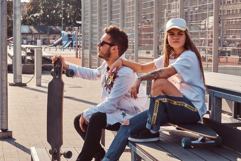 Atractive-Paar von modischen gekleideten jungen Hippies mit den Skateboards, die auf Bank an der Stadt sitzen, trägt Komplex am s lizenzfreies stockfoto