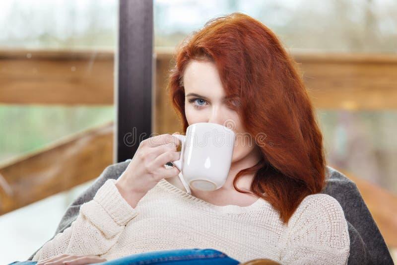 Atractive roodharige vrouw het drinken kop van koffiezitting op Schommelstoel Jong meisje met hete activerende drank royalty-vrije stock afbeeldingen
