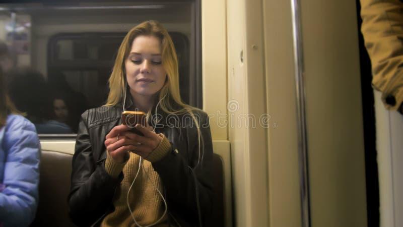 Atractive szczęśliwa dziewczyna z długim blondynka włosy w skórzanej kurtce prostuje use gadżet w metrze fotografia stock