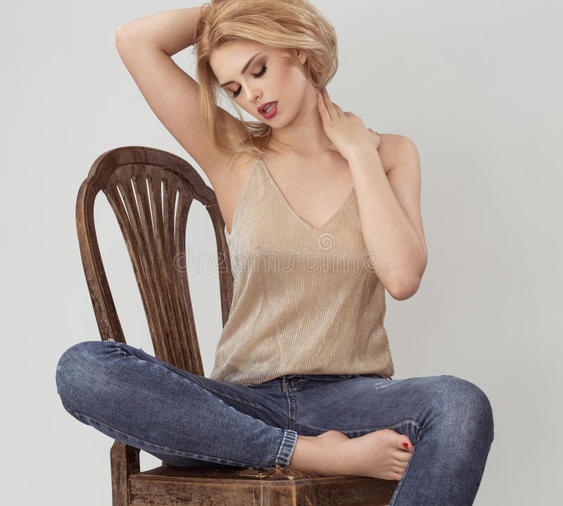 Atractive woman in gold shirt sitting on the brown chair royalty free stock photography