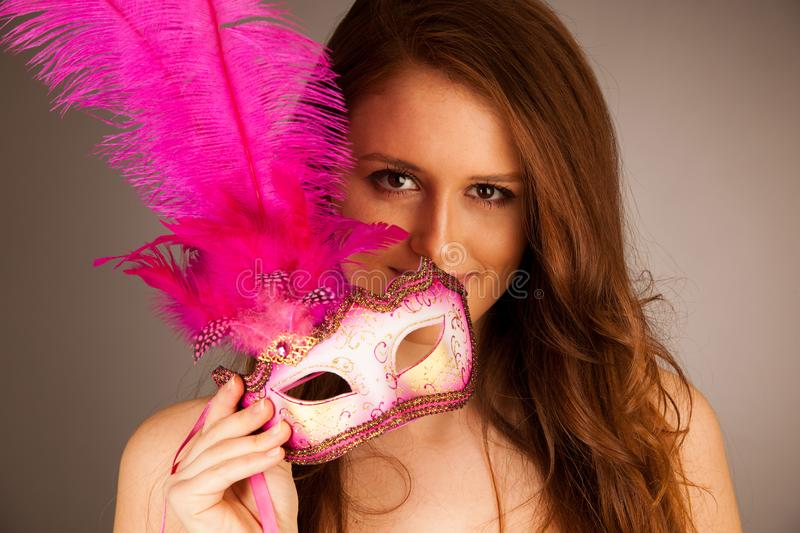 Atractive young woman with venice mask studio portrait stock image
