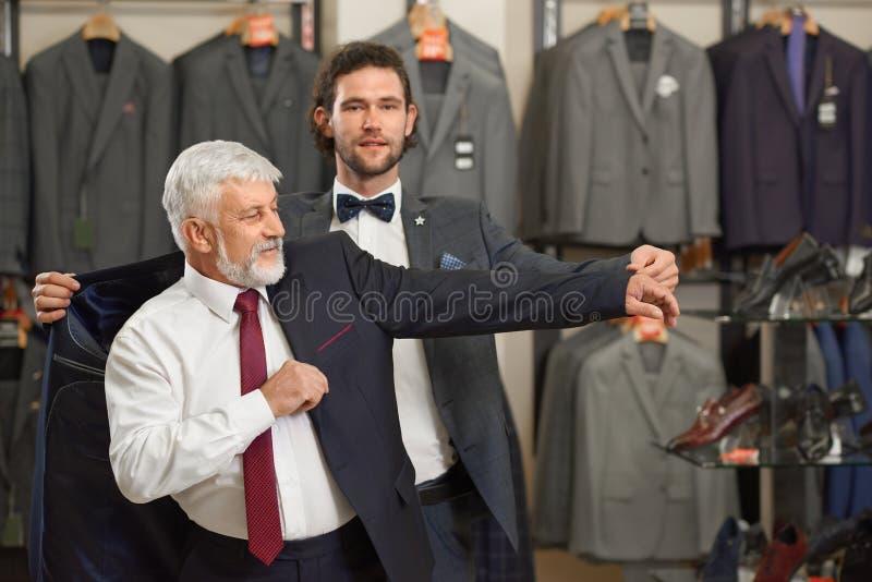 Atractivekerel en oudere grijze mens in kostuums in mannelijke opslag royalty-vrije stock afbeelding