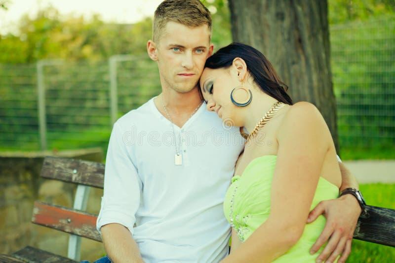 Atractivo el individuo con la muchacha se sienta y abraza en un banco fotos de archivo libres de regalías