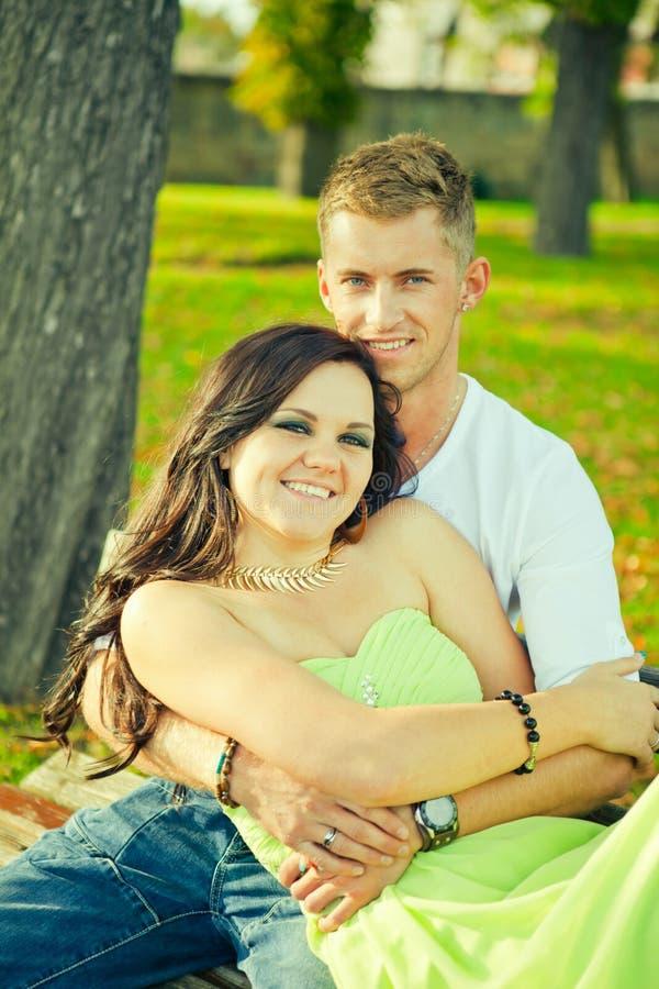 Atractivo el individuo con la muchacha se sienta y abraza en un banco fotografía de archivo