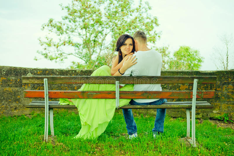 Atractivo el individuo con la muchacha se sienta y abraza en un banco imagen de archivo libre de regalías
