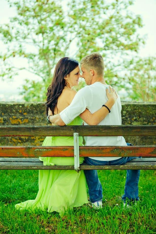 Atractivo el individuo con la muchacha se sienta y abraza en un banco fotografía de archivo libre de regalías