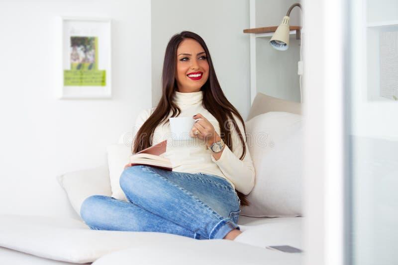 Atrakcyjna żeńska biznesowa kobieta bierze przerwę po tym jak długi dzień z filiżanka kawy i książką zdjęcie royalty free