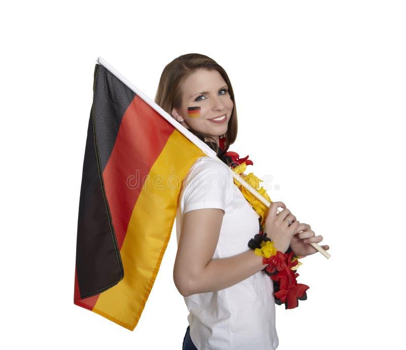 Atrakcyjna żeńska fan przedstawień niemiec flaga i uśmiechy przed białym tłem obrazy stock