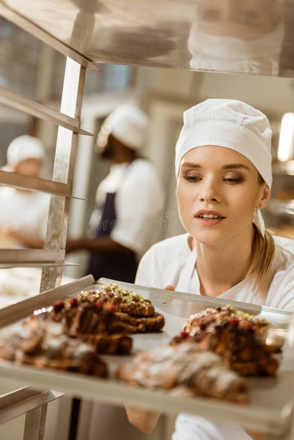 atrakcyjna żeńska piekarniana patrzeje taca świeżo piec croissants zdjęcie stock