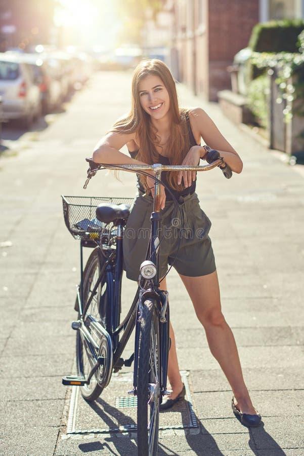 Atrakcyjna życzliwa młoda kobieta lub uczeń z jej rowerową pozycją w miastowej ulicie w lata świetle słonecznym ono uśmiecha się  fotografia royalty free