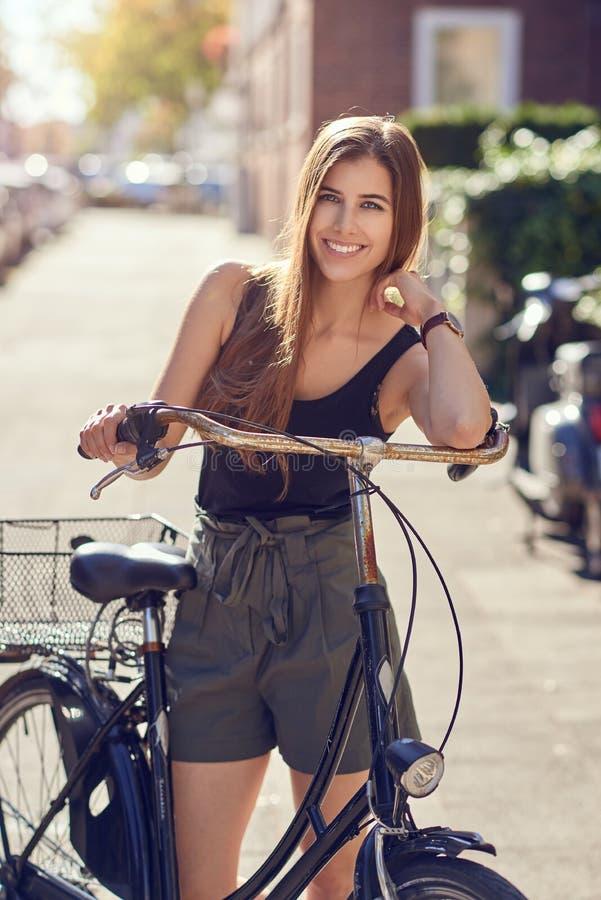 Atrakcyjna życzliwa młoda kobieta lub uczeń z jej rowerową pozycją w miastowej ulicie w lata świetle słonecznym ono uśmiecha się  obrazy royalty free