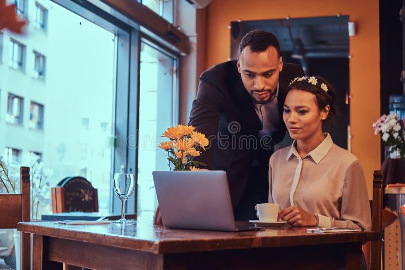 Atrakcyjna afroamerykańska para przy biznesowym spotkaniem dyskutuje pracujących momenty z laptopem przy w restauraci fotografia royalty free