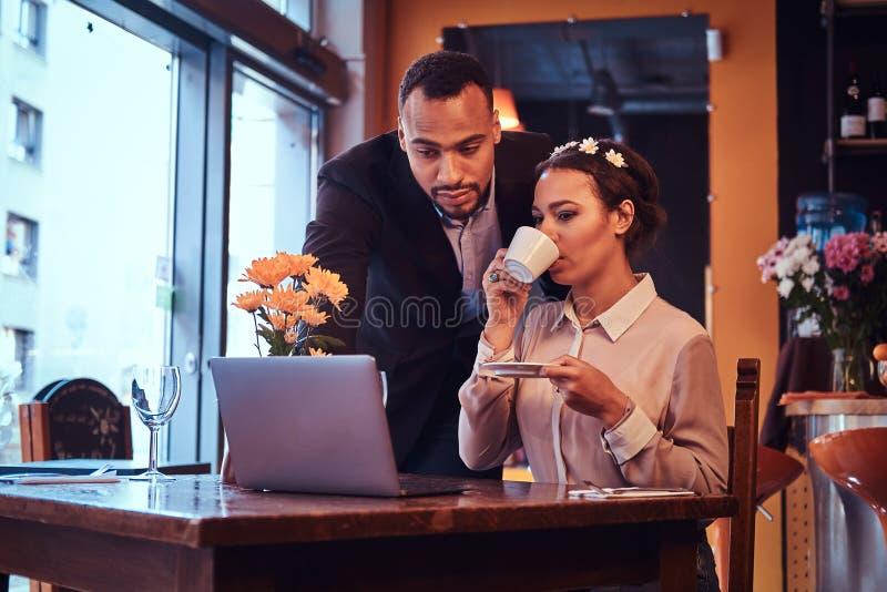 Atrakcyjna afroamerykańska para przy biznesowym spotkaniem dyskutuje pracujących momenty z laptopem przy w restauraci zdjęcie royalty free