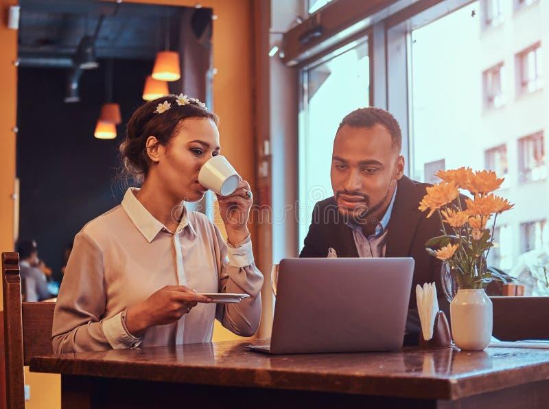 Atrakcyjna afroamerykańska para przy biznesowym spotkaniem dyskutuje pracujących momenty z laptopem przy w restauraci zdjęcia stock