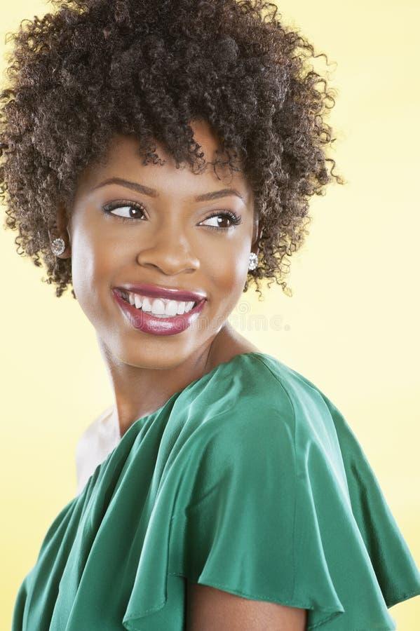 Atrakcyjna amerykanin afrykańskiego pochodzenia kobieta w daleko naramienny smokingowy patrzeć daleko od nad barwionym tłem obrazy royalty free