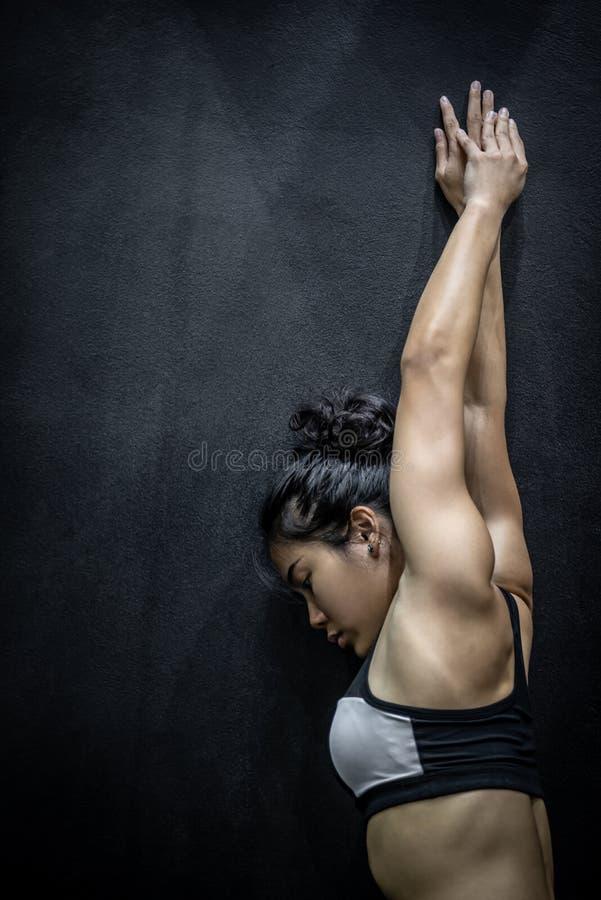 Atrakcyjna Azjatycka dziewczyny rozciągania ręka na czerni ścianie obraz stock