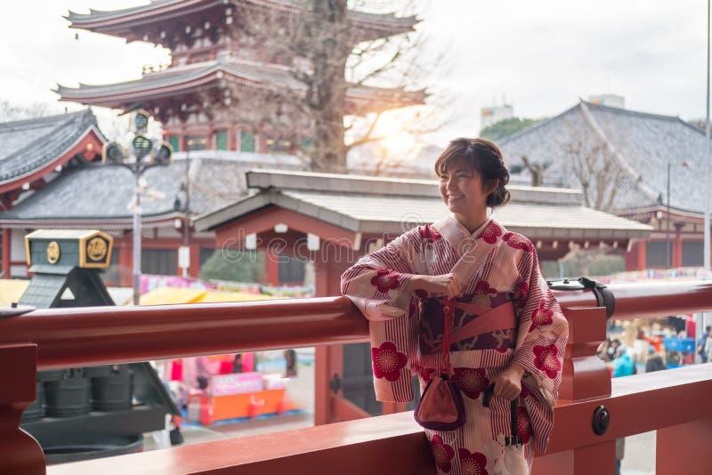 Atrakcyjna azjatykcia kobieta jest ubranym kimono przy Sensoji Asakusa świątynią, obraz royalty free