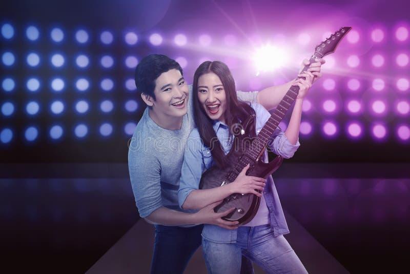 Atrakcyjna azjatykcia para bawić się gitarę obraz stock
