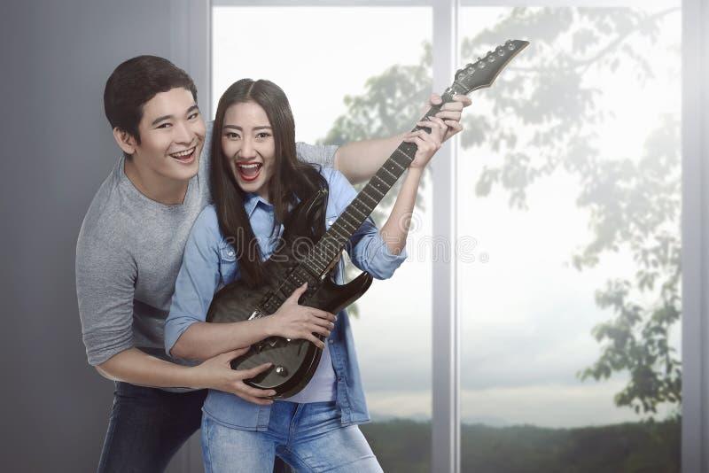 Atrakcyjna azjatykcia para w miłości bawić się gitarę zdjęcia royalty free