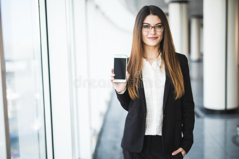Atrakcyjna biznesowa dama trzyma smartphone, wskazujący na nim, patrzejący kamerę i ono uśmiecha się zdjęcie stock