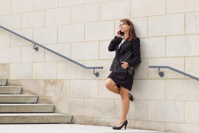 Atrakcyjna biznesowa kobieta opowiada na mądrze telefonie zdjęcie royalty free