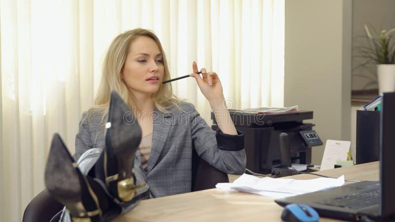 Atrakcyjna biznesowa kobieta w kostiumu pracuje z dokumentami w biurze, iść na piechotę na stole obrazy stock