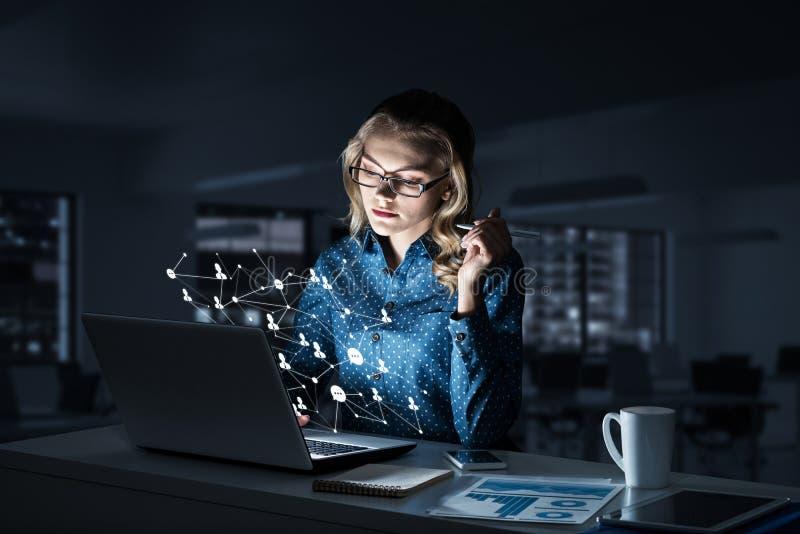 Atrakcyjna blondynka jest ubranym szkła w ciemnym biurowym używa laptopie M zdjęcie royalty free