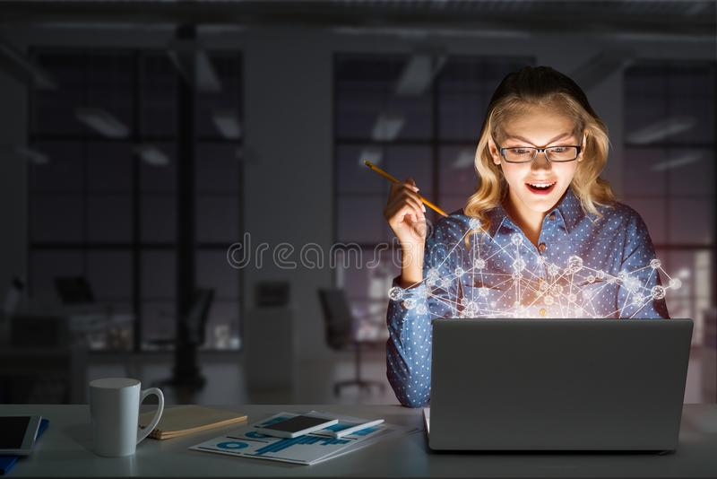 Atrakcyjna blondynka jest ubranym szkła w ciemnym biurowym używa laptopie Mieszani środki zdjęcie stock