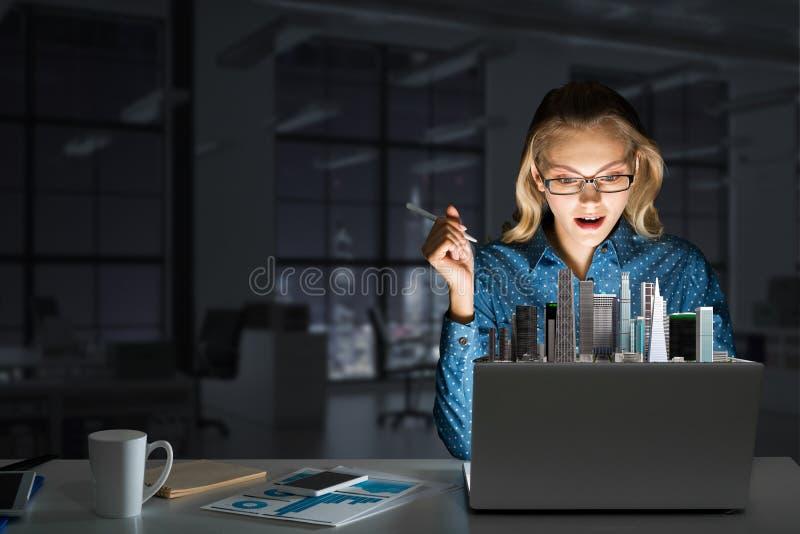 Atrakcyjna blondynka jest ubranym szk?a w ciemnym biurowym u?ywa laptopie Mieszani ?rodki obrazy royalty free