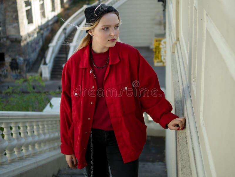 Atrakcyjna blondynka modnisia dziewczyna w trykotowej czerwieni kurtce i czarnym kapeluszu stoi na schodkach pod mostem fotografia royalty free