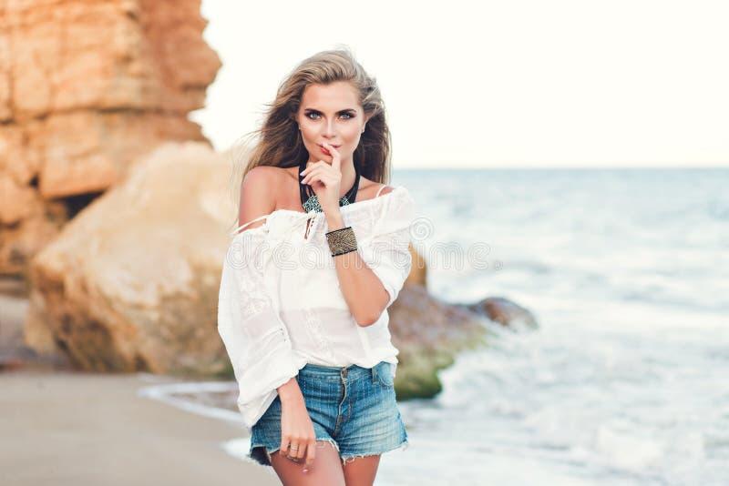 Atrakcyjna blondynki dziewczyna z długie włosy pozuje na plażowym pobliskim morzu Jest ubranym białą koszula z nagim ramieniem i zdjęcia royalty free